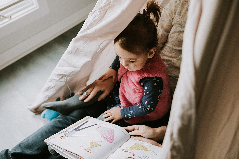 Girl reading books in tent