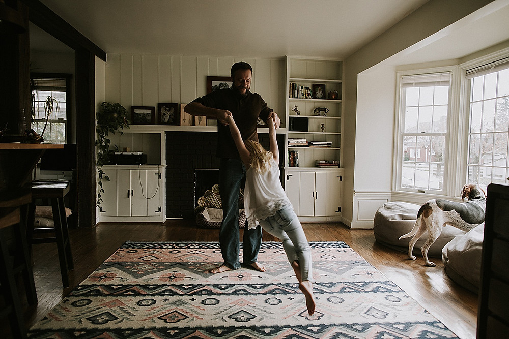 Dad dancing with daughter in living room