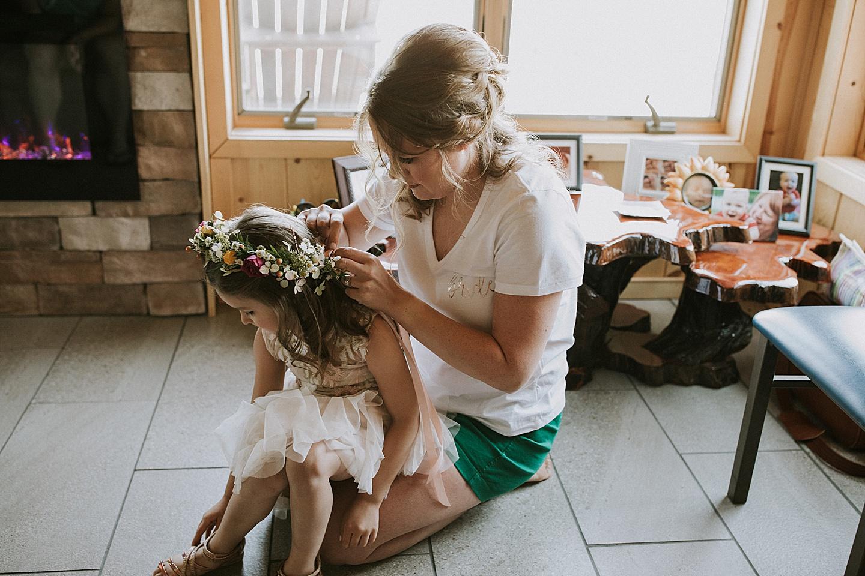 Bride putting flower crown on flower girl before wedding