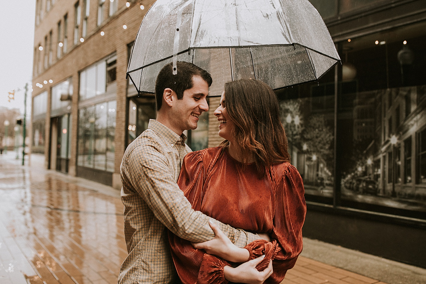 Couple portraits taken outside in the rain with clear umbrella