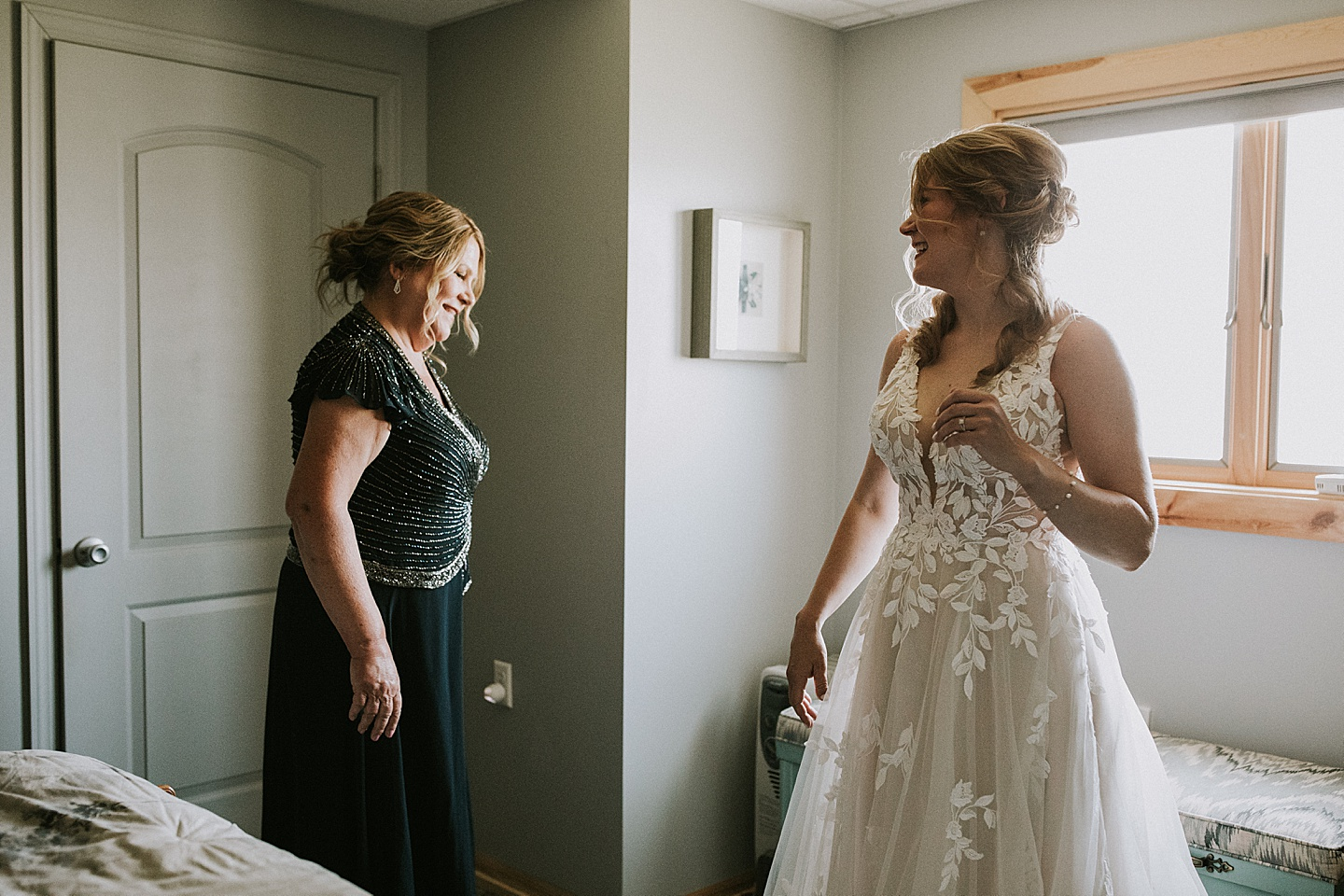 Bride and mom smiling at each other