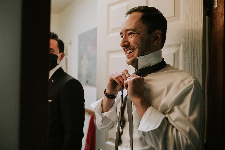 Groom putting on tie before wedding