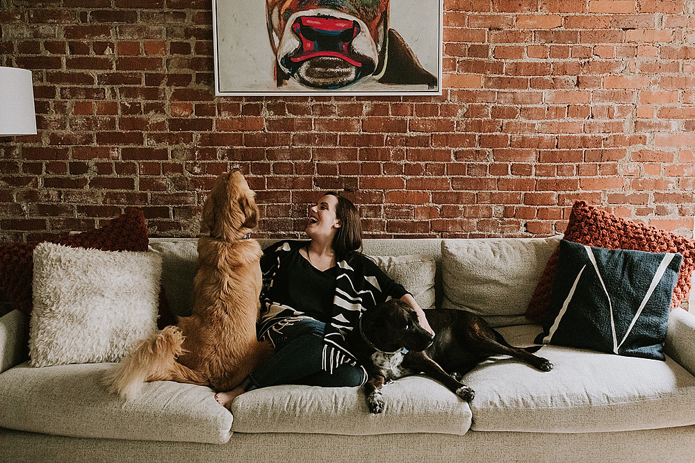 Woman sitting on couch with her dogs