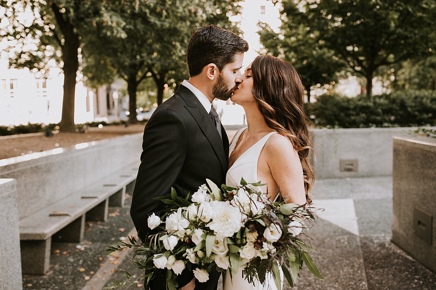 Couple kissing during wedding portraits