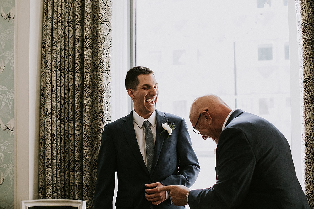 Dad laughing with son before wedding