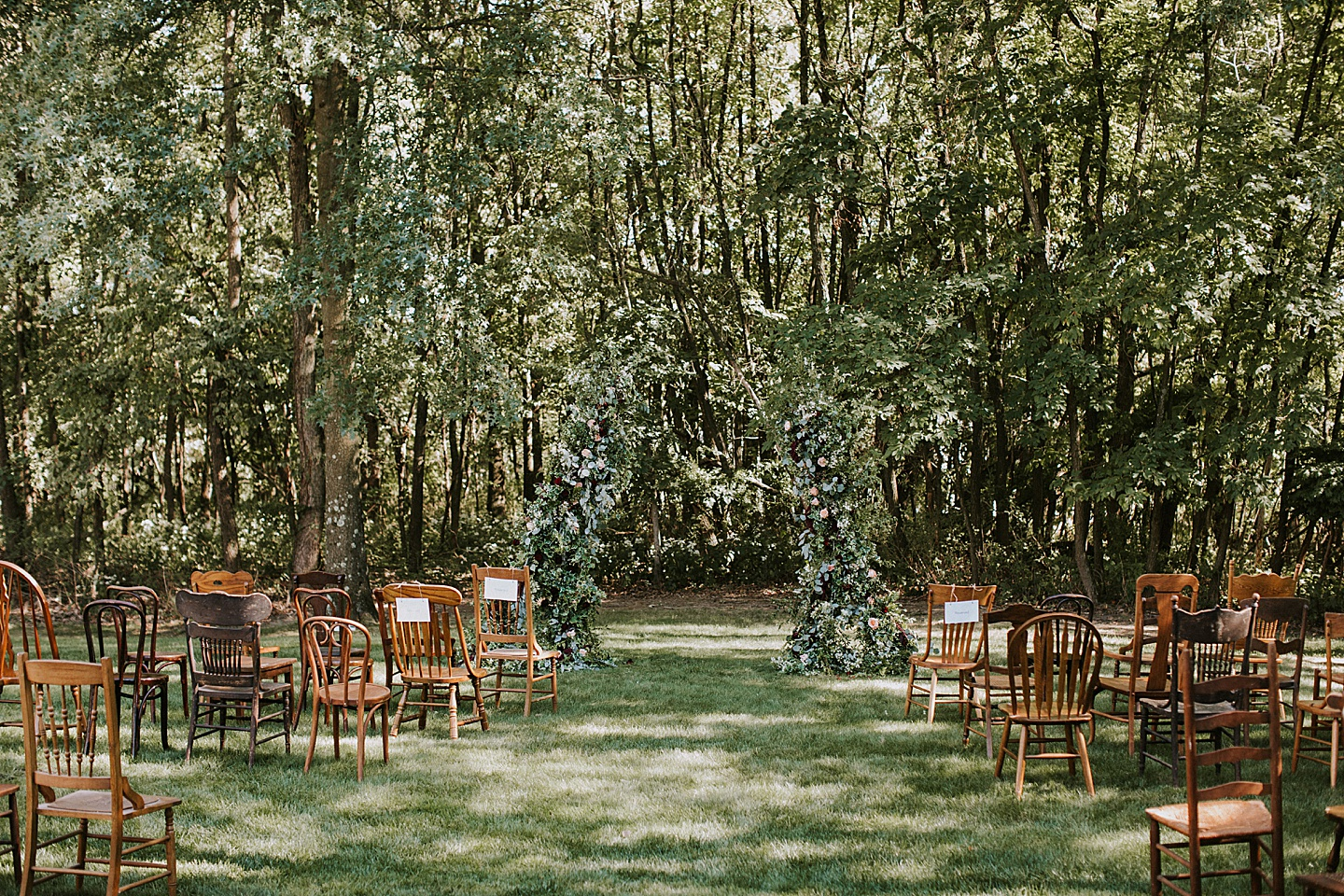 Antique chairs at wedding ceremony with floral altar