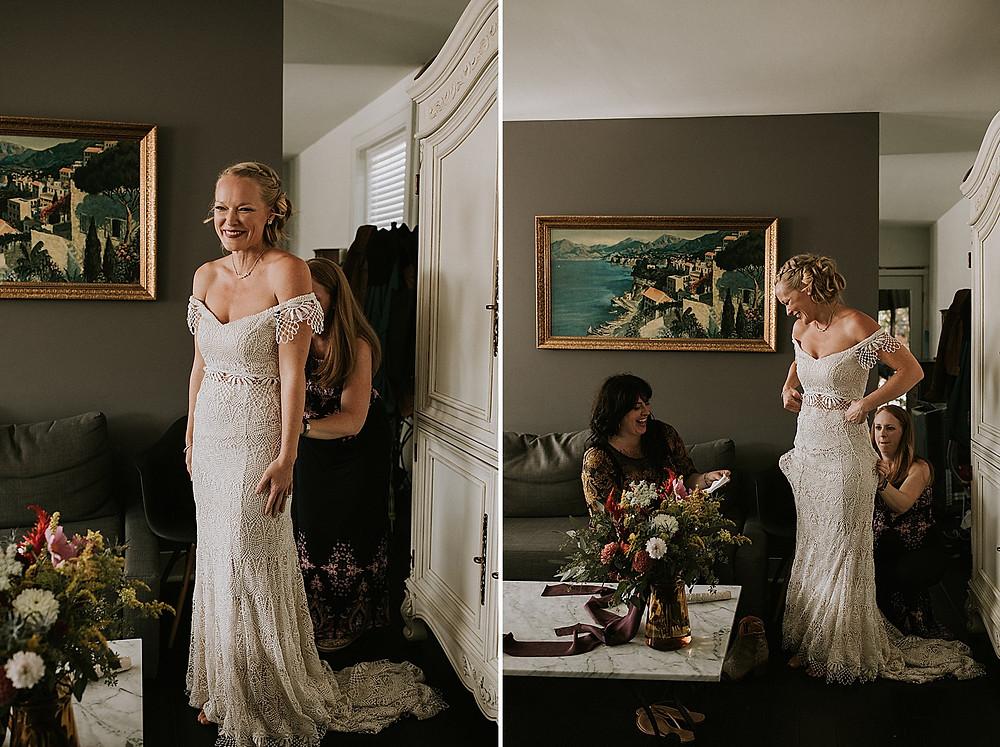 Bride putting on dress before wedding
