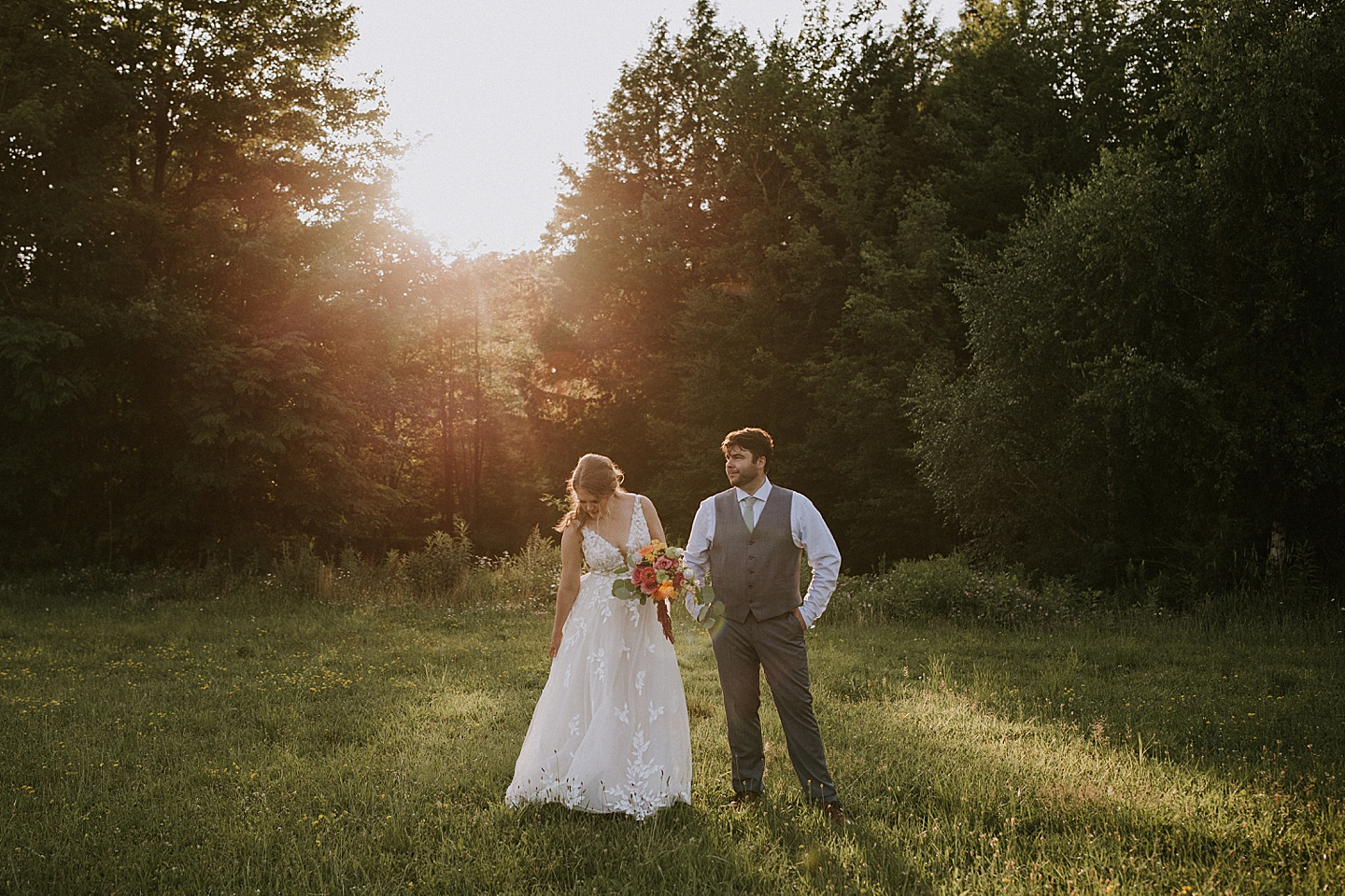 Bride and groom standing in grass