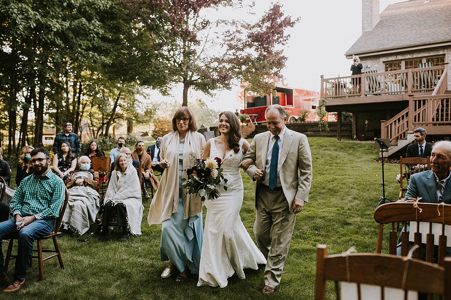 Bride walking down the aisle with both parents in backyard Pittsburgh wedding