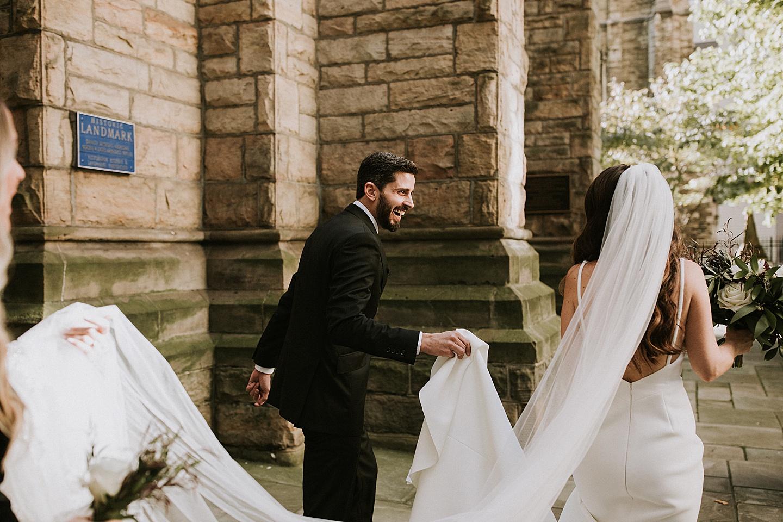 Groom carrying bride's dress