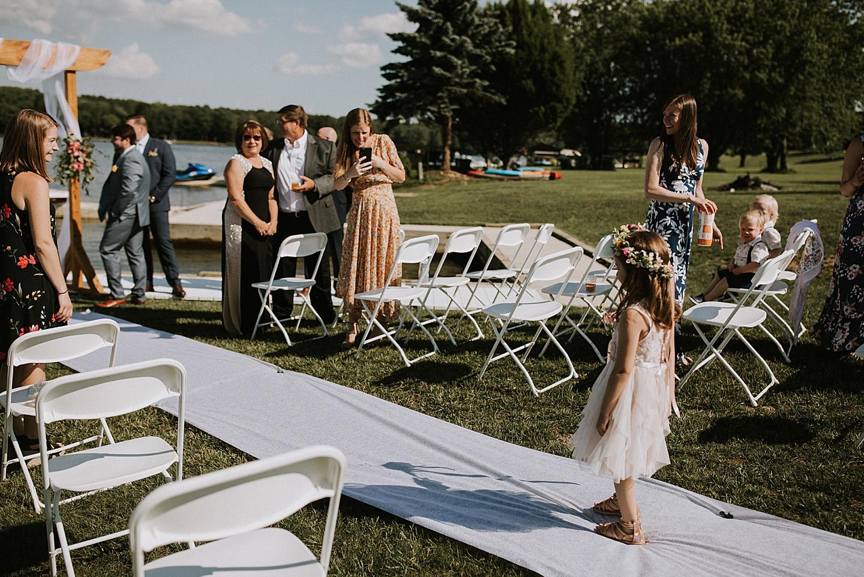 Flower girl walking down the aisle at wedding