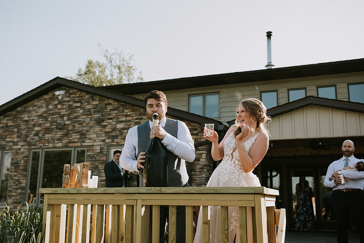 Groom opening giant bottle of champagne at wedding