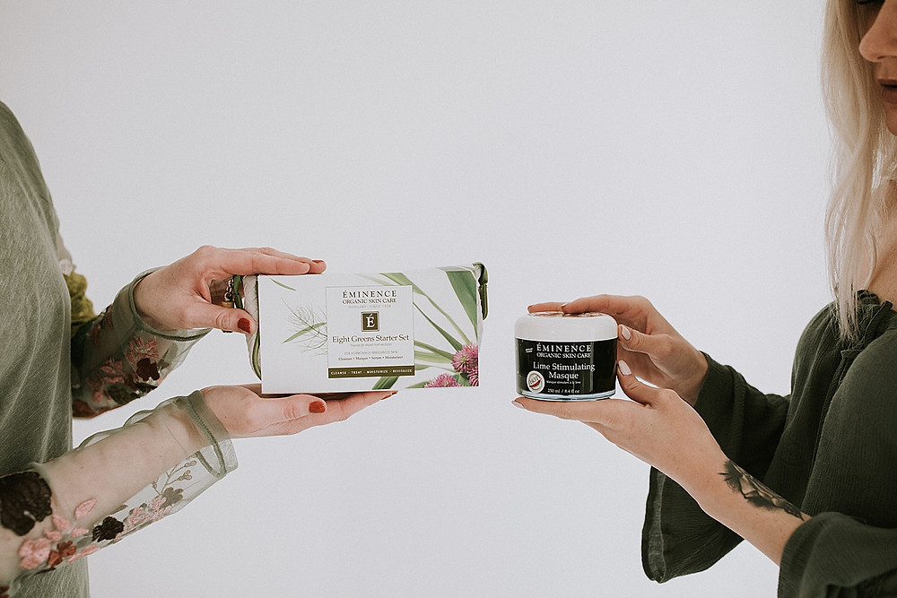 Women holding up skin care products at photoshoot