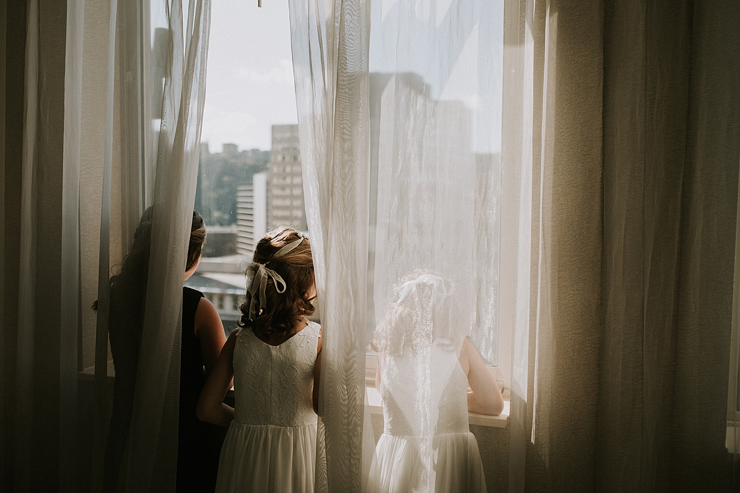 Flower girls looking out the window before wedding