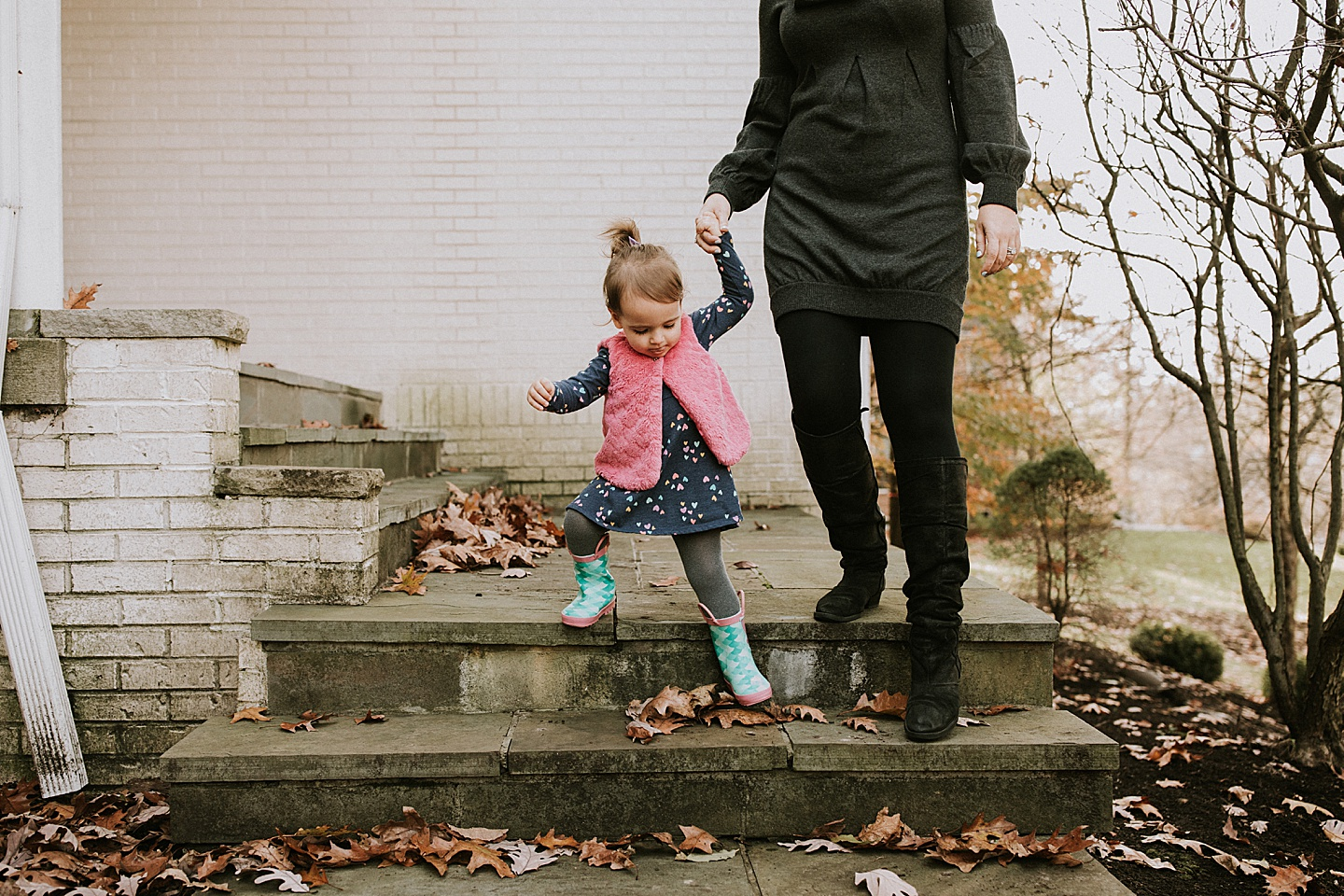 Girl walking down the stairs holding mom's hand
