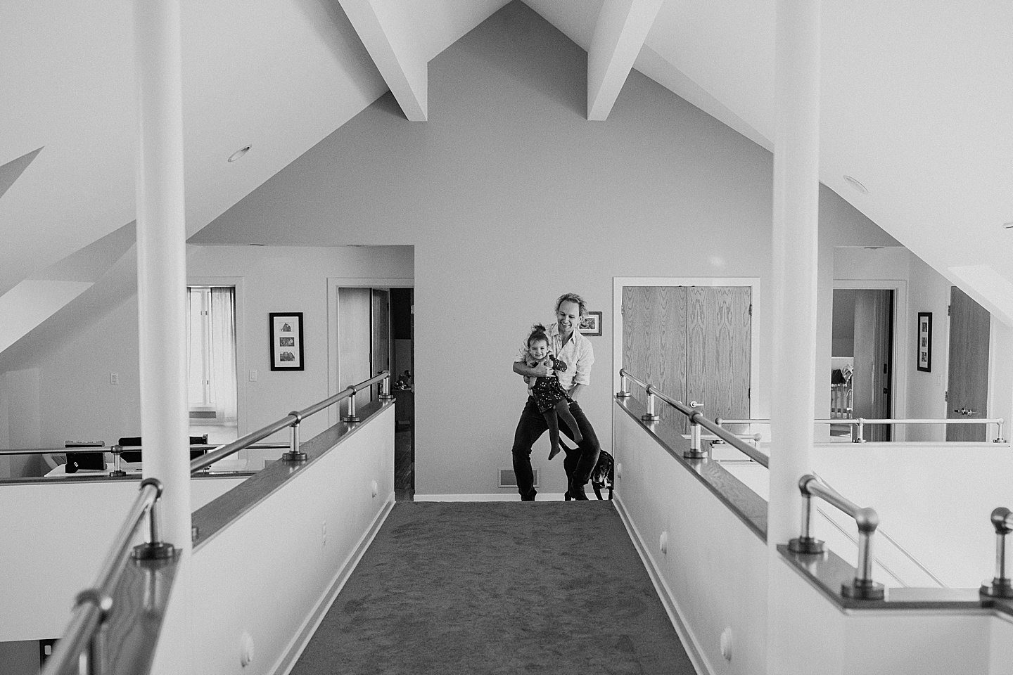 Dad carrying daughter around home