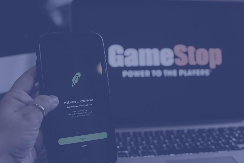 Robinhood logo on phone and Gamestop logo on laptop