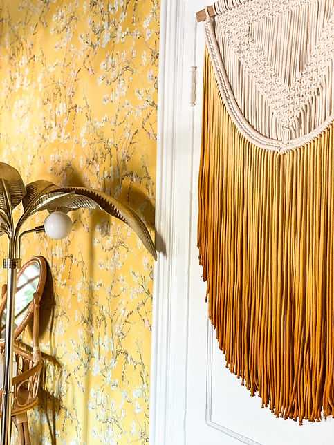 A close up photo of a yellow wallpapered wall in Room 6 with a macrame weaving and a gold palm tree