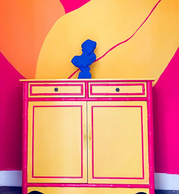 A mural of a hot pink wall with bright yellow leaves and a cabinet painted to match