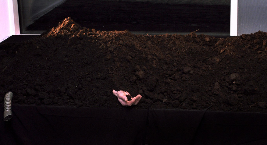 "Buried man. Performance ""Black Earth"""