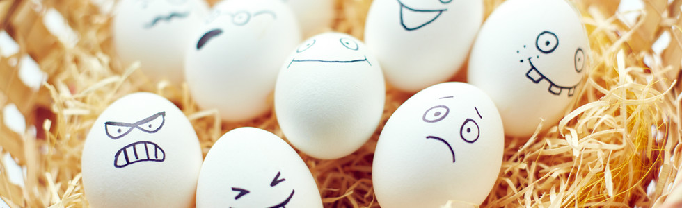 Basket with funny eggs with painted face