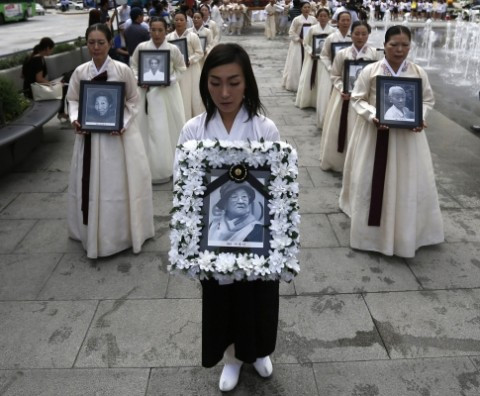 Women carry portraits commemorating Koreans who were made sex slaves by the Japanese during World War II. Seoul. (Kim Hong-Ji/Reuters)