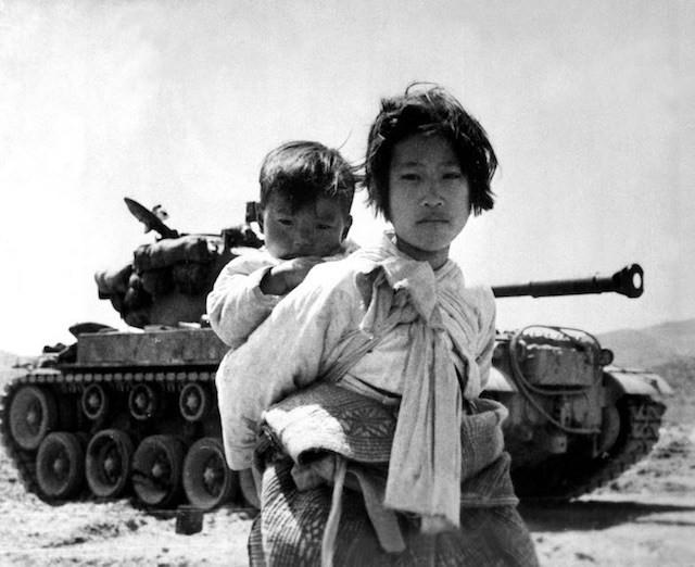 With her brother on her back a war weary Korean girl tiredly trudges by a stalled M-26 tank, at Haengju, Korea. June 9, 1951. Maj. R.V. Spencer, UAF. (Navy) NARA FILE #: 080-G-429691 WAR & CONFLICT BOOK #: 1485