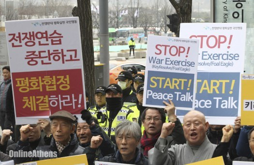 """Protesters demand halt to largest ever U.S.- South Korea war games in front of U.S. Embassy in Seoul, March 7, 2016.Signs at left read: """"Stop, the joint military exercises between the U.S. and South Korea (""""AP Photo/Ahn Young-joon)"""