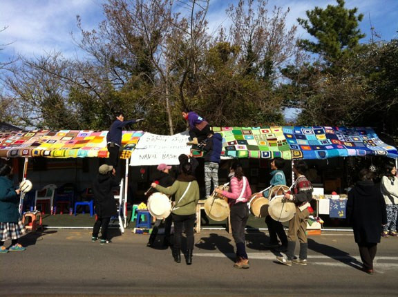 Gangjeong villagers and activists decorate the streets with colorful woolen squares knitted by supporters of the anti-base struggle. Traditional drummers play in the foreground.