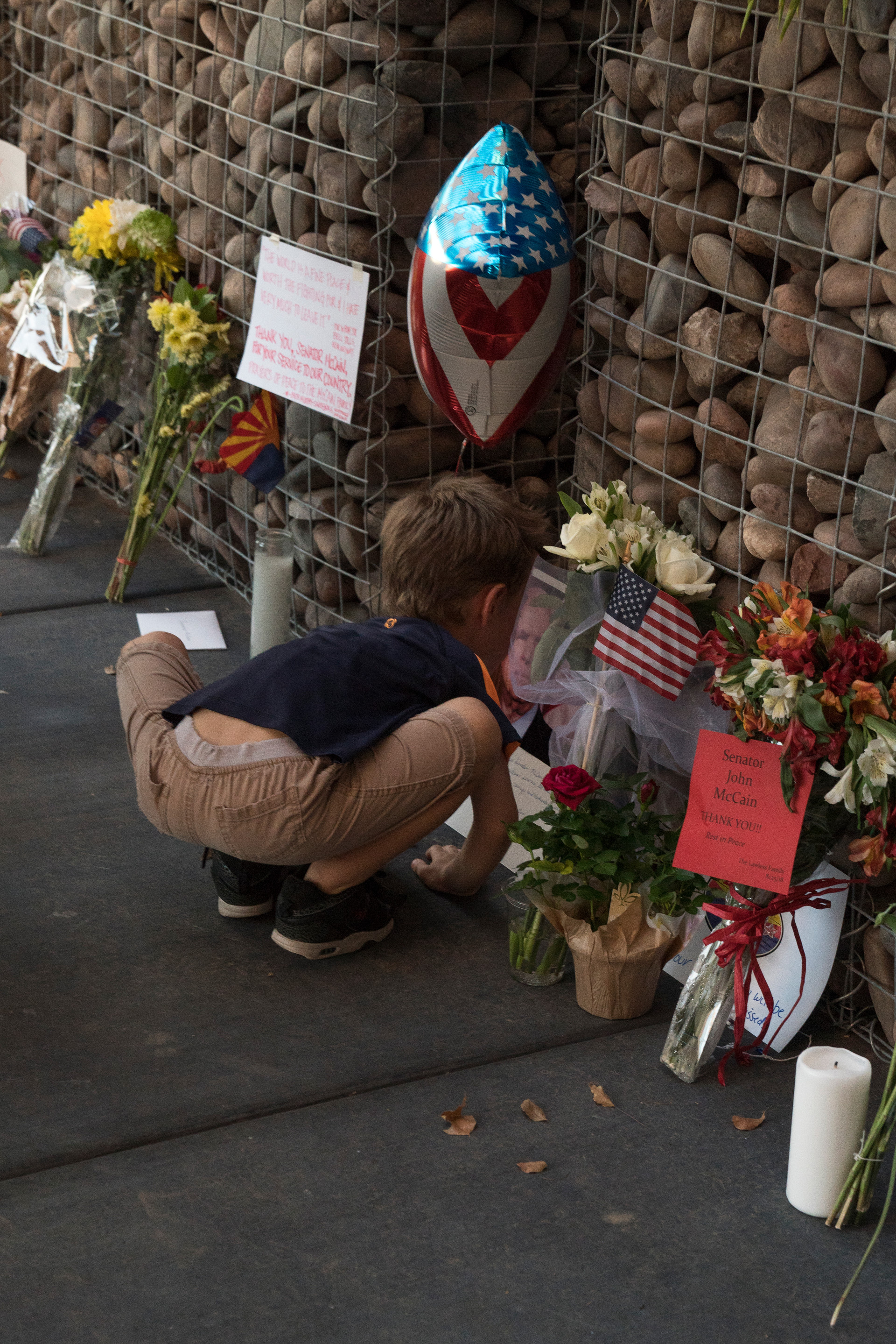 A young boy kisses a portrait of the late Senator John McCain at the Vietnamese Association of Arizona memorial for McCain at his office in Phoenix, Arizona on Sunday, August 26, 2018.