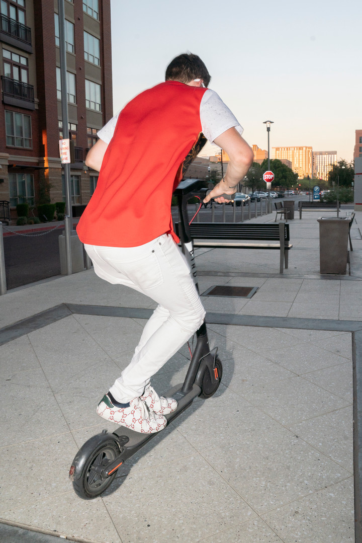 Brandon Stewart jumps a Bird scooter outside of the W6 apartment building in Tempe, AZ.