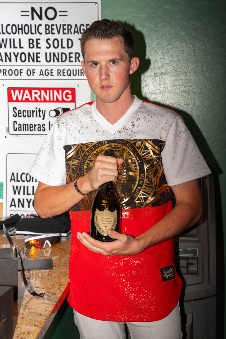 Brandon Stewart shows off his $250 bottle of Dom Perignon inside the convient story inside of the W6 in Tempe, AZ.