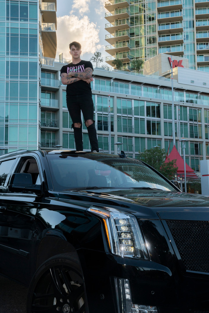 Elijah James stands on top of his Cadillac Escalde in front of the W6 apartments in Tempe, AZ.