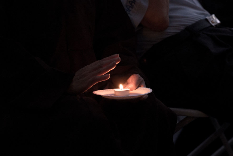 Attendee holds candle at the Vietnamese Association of Arizona memorial for John McCain at his office in Phoenix, Arizona on Sunday, August 26, 2018.