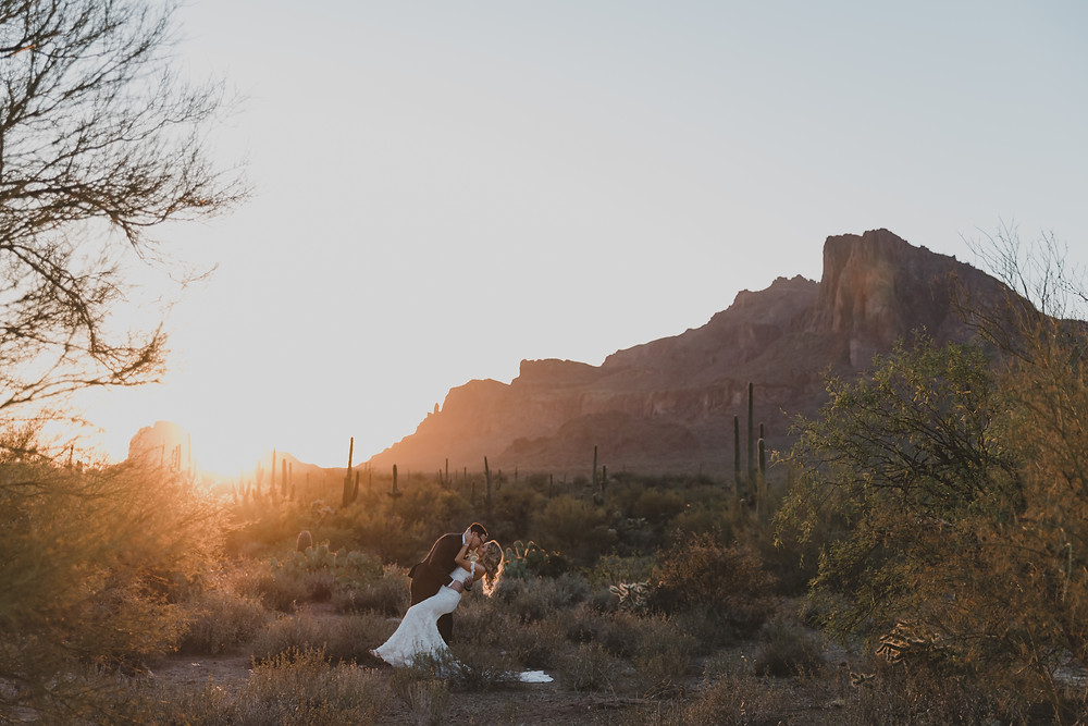 couple kissing with beautiful sunset and mountains in the background
