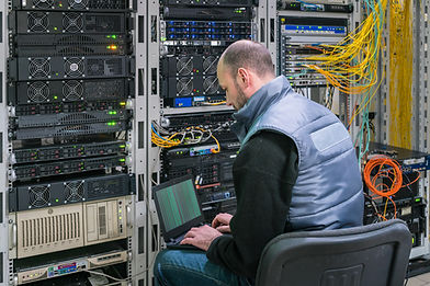 A man with a laptop sits in a server room. A technician works near the racks of a modern d