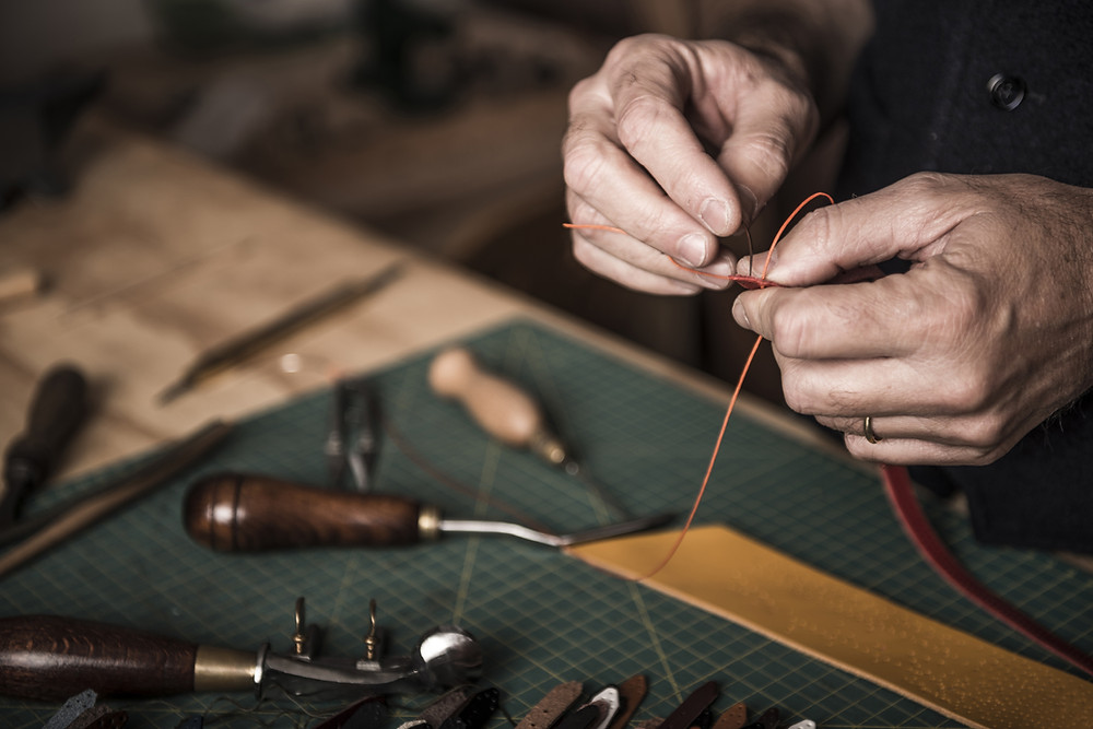 Leather maker craftsman with tools making a belt