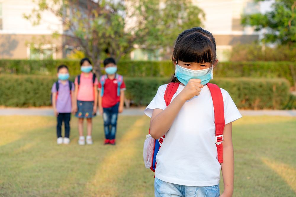 Girl in mask with a backpack with three friends in the background