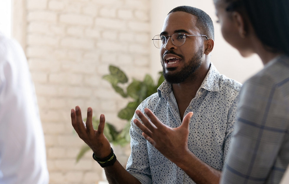 A young Black man speaks with a group of colleagues