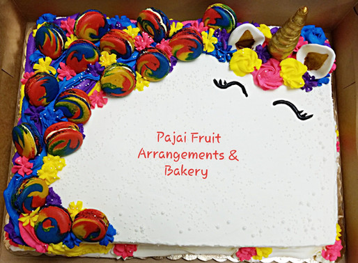 Half sheet Unicorn cake with rainbow color and macaroons.