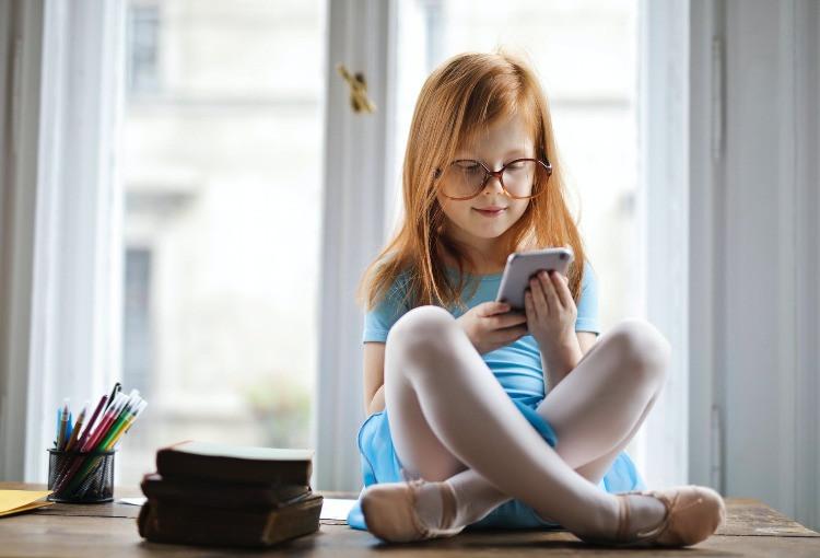 bambina con in mano un cellulare