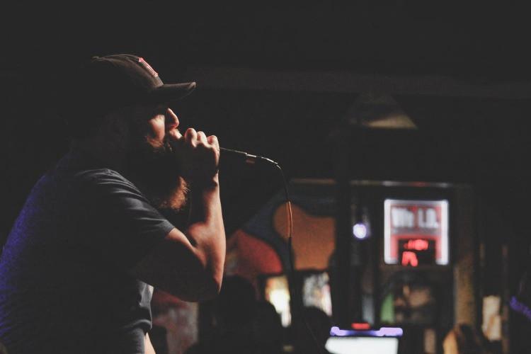 Rapper in un bar con un microfono in mano che canta per un pubblico.