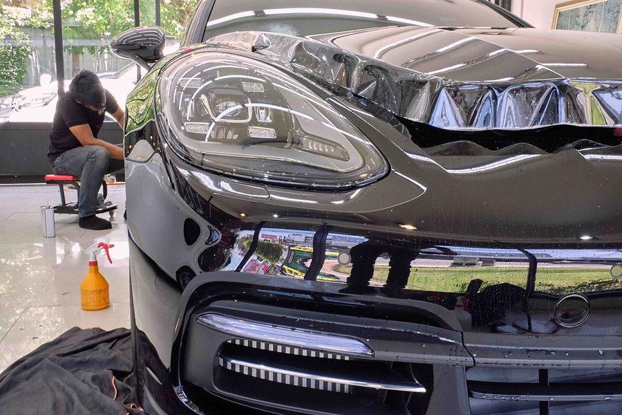 Black Porsche Receiving Paint Protection PPF Headlight