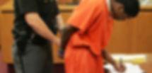 black-defendant-signing-plea-in-court.jp