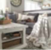 Cozy, plush grey couch with farmhouse style coffee table.