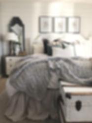 Master bedroom with shiplap walls and custom headboard.