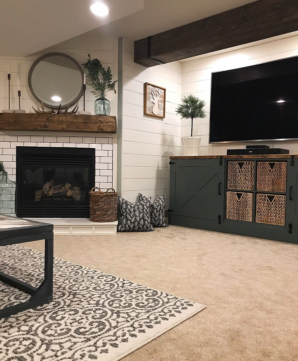 corner fireplace in basement living room with subway tile and rustic mantel