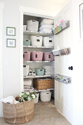 Organized linen closet with labelled baskets.