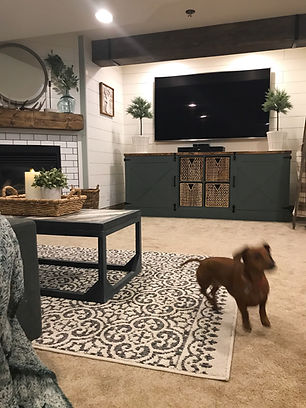 Basement entertainment area with large TV and fire place.