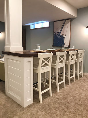 Basement bar with farmhouse style chairs.